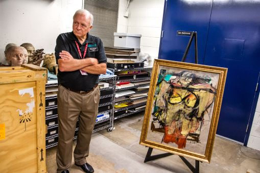 """UA Museum of Art security officer Jim Kushner stands guard during the authentication and inspection process of the returned """"Woman-Ochre."""""""